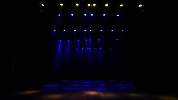 Sok világító berendezés a koncertterem üres színpadán.