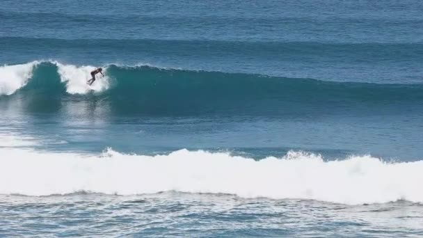A surfer rides a wave in the surf at the ocean blue in the surf spot.
