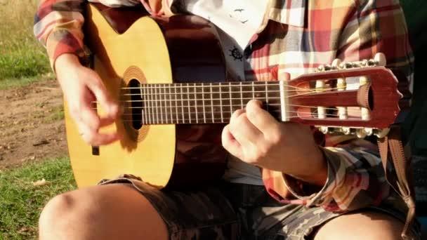 Ruce muže, který hraje na kytaru během letního pikniku na přírodě.