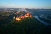 Letecký pohled na krásné, Moravský královský hrad Veveří nebo Burg Eichhorn, na skále nad vodní přehrady na řece Svratce. Velký hrad nad mlžným stromy v ranním světle. Letecká fotografie.