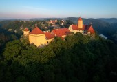 Photo Aerial view of beautiful, Moravian royal castle Veveri or Burg Eichhorn, standing on a rock above water dam on river Svratka. Large castle above misty trees in early morning light. Aerial photography.