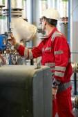 Energiewirtschaft. Ein Techniker in roten Overalls und weißem Helm überprüft die Heizparameter. Heizungstechnologie zur Wasserverteilung. Servicearbeiten in der Energiewirtschaft.