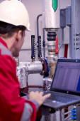 Energiewirtschaft. Ein Techniker in roten Overalls und weißem Helm überprüft die Heizparameter. Heizungstechnologie zur Wasserverteilung. Servicearbeiten in der Energiewirtschaft. Heizsaison.