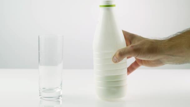 Nalijte mléko do sklenice, na bílém pozadí.Mléko ve skleně.Proud jogurtu.