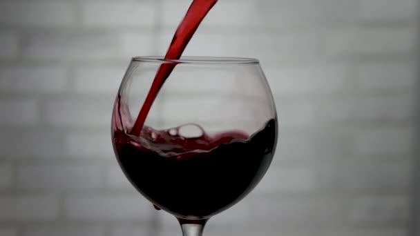 Öntsön vörösbort egy borospohárba egy üvegből, bort egy pohárba.