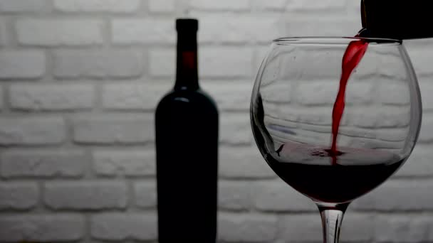 Pouring red wine from a bottle into a wine glass on a white brick wall background close-up