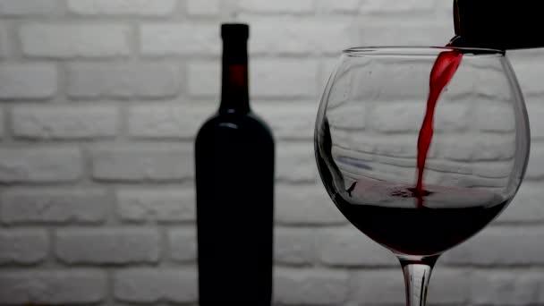 Nalití červeného vína z láhve do sklenice na bílém pozadí cihlové zdi