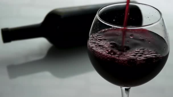 Pouring red wine into a wine glass,a bottle of wine with a glass of wine