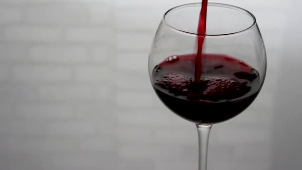 Pouring wine into a glass on a white background.Semi-sweet red wine in a glass,close-up