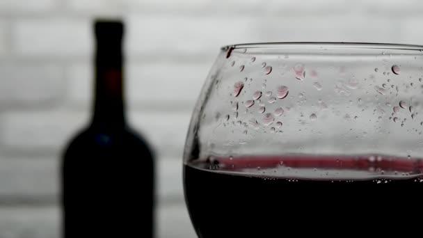 Kapka vína spadne do sklenice, láhev červeného vína a sklenku vína