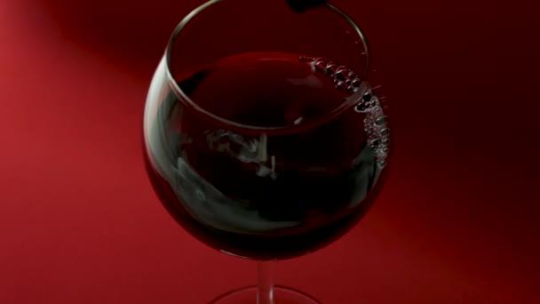 Tropfen tropfen von einer Flasche Wein in ein Glas auf rotem Hintergrund, ein Glas Rotwein in Großaufnahme von oben