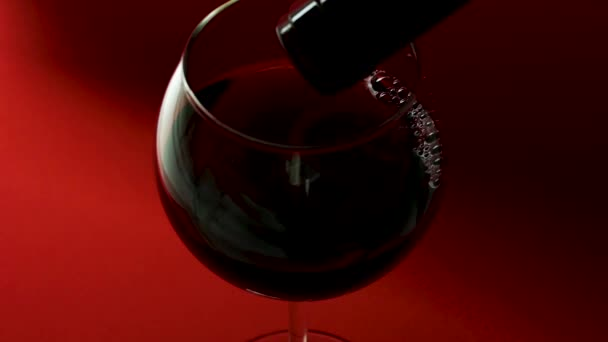 Pour red wine from a bottle into a glass on a red background. Glass of red wine close-up
