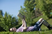 Fotografia Disabled young man with foot prosthesis read book on grass