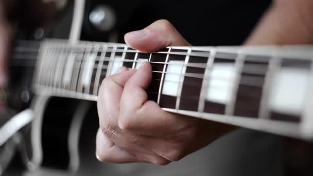Hudebník v zatáčkách struny na elektrickou kytaru při hraní, elektrické hudební nástroje, hrát hlasitá kytara, rocková kytara