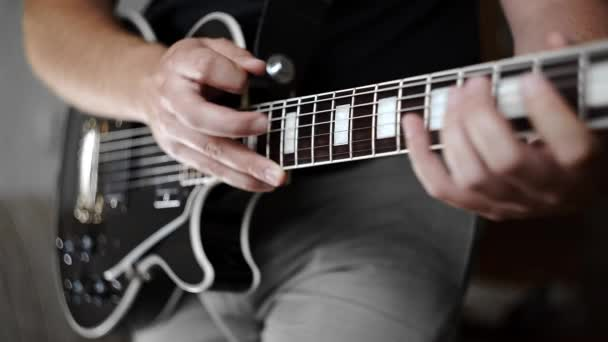 Musician uses tapping technique to play the electric guitar,playing on electric musical instruments, playing loud on the guitar, rock guitars