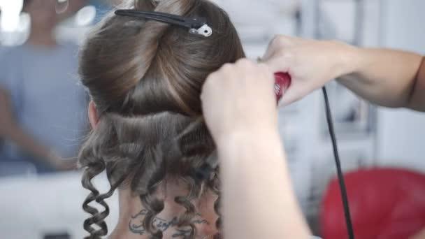 Stylist teszi göndör afro frizura a nő forró curling haj, frizura, frizurát a szépségszalonban folyamata