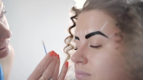 Stylist makes eyebrow correction for curly beautiful woman at the ...