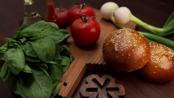 Video ukazuje přísady pro výrobu lahodné karbanátky, svěží zelení a zeleniny pro vaření, housky se sezamem, vaření hamburgerů, fastfood receptů, vaření doma
