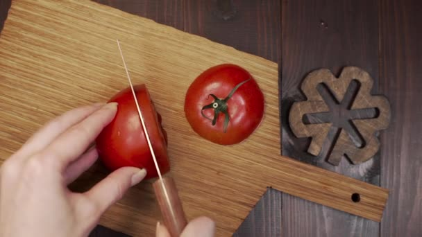Chef cuts the tomato by sharp steel knife on the wooden board, cooking the salad, making of vegetable meal, healthy raw food