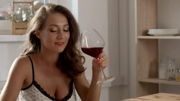 Sexy a atraktivní žena v upřímné šaty sedí u stolu v kavárně, nápoje červené víno z jejího skla a textových zpráv na svém smartphonu s úsměvem, atraktivní žena je sama v baru, Žena texty k ní