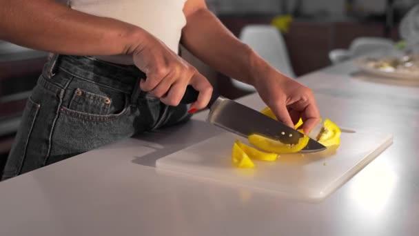 Sexy žena škrty žlutá paprika s ostrým nožem na desce, Žena kuchaři zeleninové jídlo v kuchyni, takže těsto, pekařství a chléb