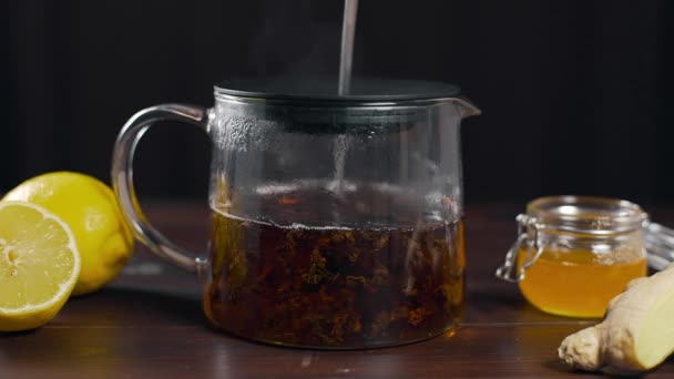 Brewed black tea is stired in the glass teapot with long spoon, vitamin tea with lemon, ginger and honey, drink against sickness, hot drinks