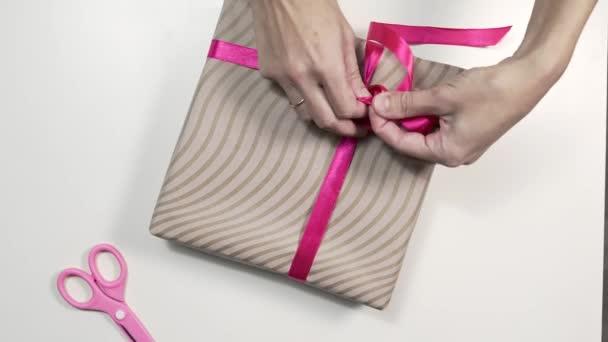 Zblízka střílel z rukou Zenske jsou vázání mašlí na krabičce, balení dárky v krásném papíře, diy wraping