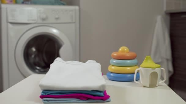 saubere Babykleidung an der Wäscherei, in der Wäscherei, am Waschtag, mit der Waschmaschine, beim Waschen von Babykleidung, 4k uhd Filmmaterial