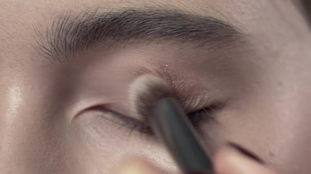 Macro shot of applying makeup to the womans eyelid, evening makeup, smokey eyes, makeup in progress, close up makeup