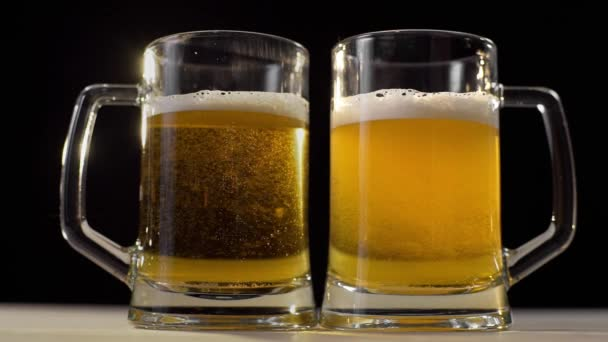 Két sör szemüveg két ember, buborékok a sör, 1080p 60 fps öntötte a habos arany világos sör a fekete háttér, a sör barátja, italok
