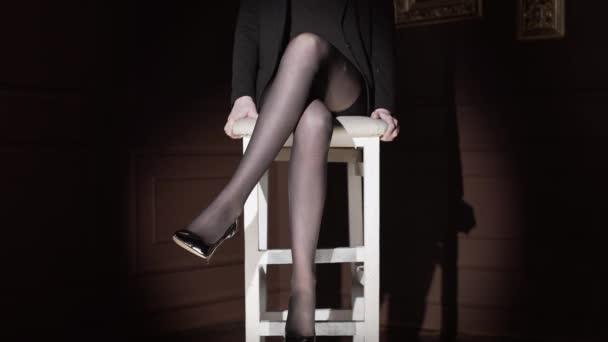Donna sexy si siede sul seggiolone in calzamaglia di pois e scuotere la gamba in scuro, lungo sexy womans piedini in calze, le gambe della donna nel cerchio di luce, full hd di alta qualità