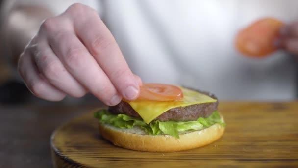 Chef szakácsok Burger és hozza a friss szeletelt paradicsom bele, hogy hamburgert a gyorsétteremben, 4k Uhd 60p ProRes HQ 422