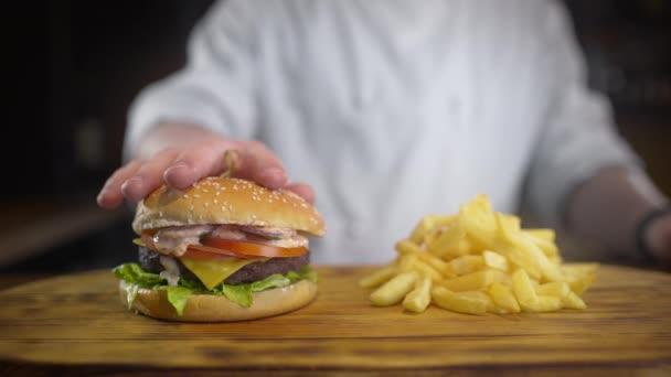 Šéfkuchař stlačuje šťavnatý Burger s omáčkou v pomalém pohybu, vaří hamburgery a hranolky v restauraci rychlého občerstvení, výborné nezdravé jídlo, 4k UHD 60p ProRes HQ 422