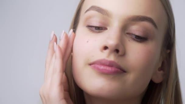 Fiatal csinos nő alkalmazza arckrém az arccsontok, alkalmazása krém körkörös mozgások, bőrápolás, természetes kozmetikumok, arcápolás, 4k Uhd Prores Hq 422