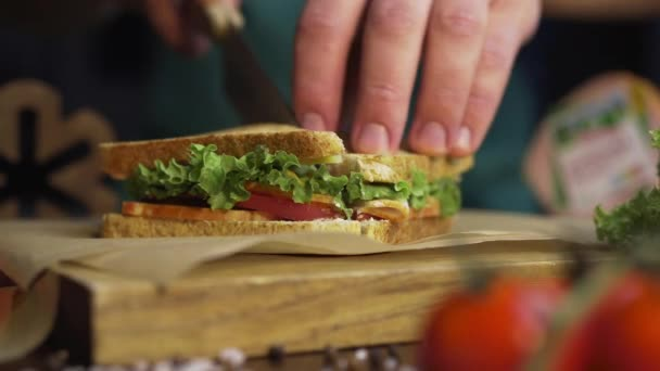 Man cuts club sandwich in a half by sharp knife on a wooden board at the kitchen, making of the fastfood at home, chef is cooking sandwich, Full HD Prores HQ 422