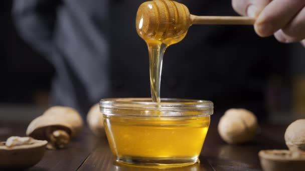 Šéfkuchař promáchne dřevěný medový klacek k skleněné misce tekutým medem, vaří s medem, sladká jídla s přírodními ingrediencemi, zdravé jídlo, Full HD 422 HQ