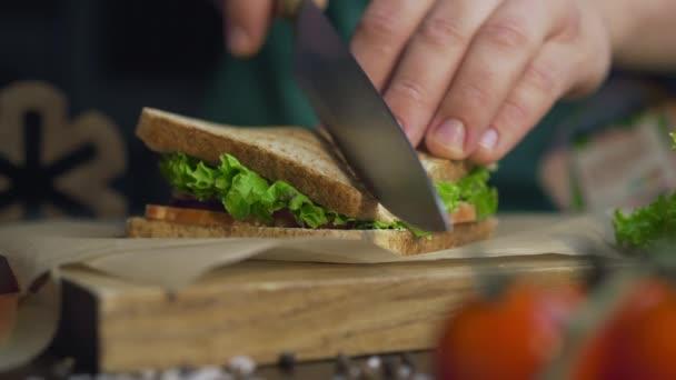 Az ember félbevágja a klub szendvicset éles késsel egy fából készült asztalon a konyhában, hogy a gyorsétterem otthon, séf főzés szendvics, 4k Uhd Prores Hq 422