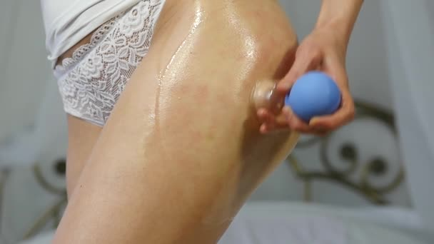 woman doing anti-cellulite vacuum massage therapy on her buttocks, self-massage in home. slow motion