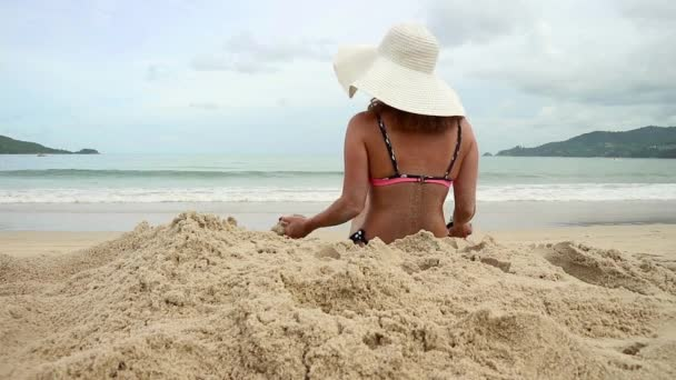 Cute woman in a white broad-brim resting on a sunny sandy beach