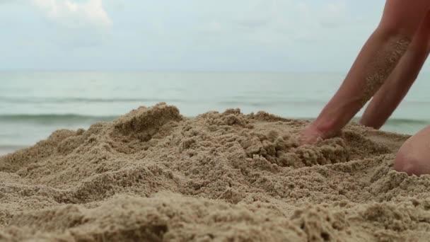 Womans kezét, játék-val homok-egzotikus tengerparti és homályos óceán hátteret. nyári vakáció koncepció