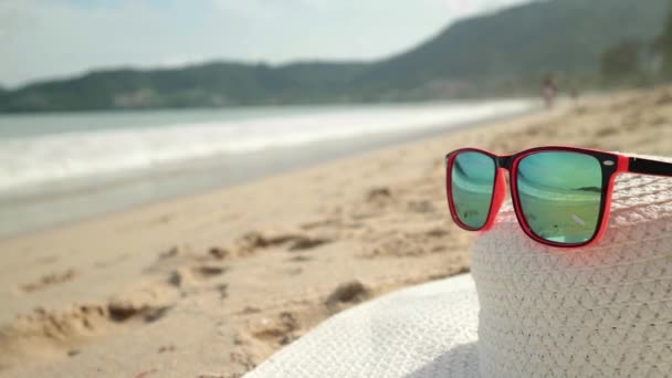 Sunglasses and white broad-brim lying on a sand. In a sunglasses reflected sea, waves and sky.