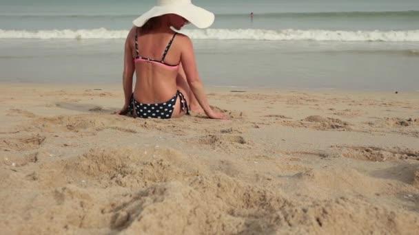 Nő a bikini és a nap kalap-homokos tenger paradise strand napozás közben hátulnézet