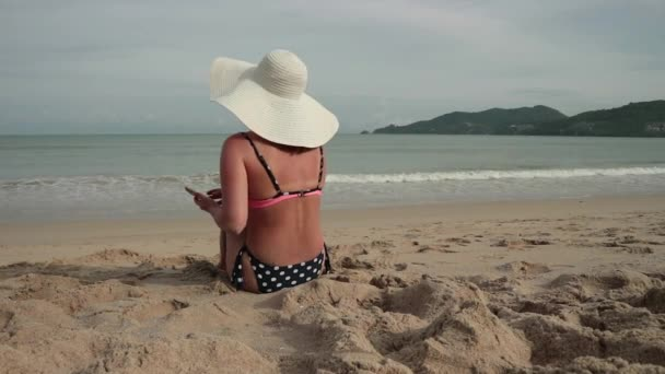 Young woman using cellphone while sunbathing at the beach. Beautiful girl in a bikini and sun hat takes pictures and writes text message