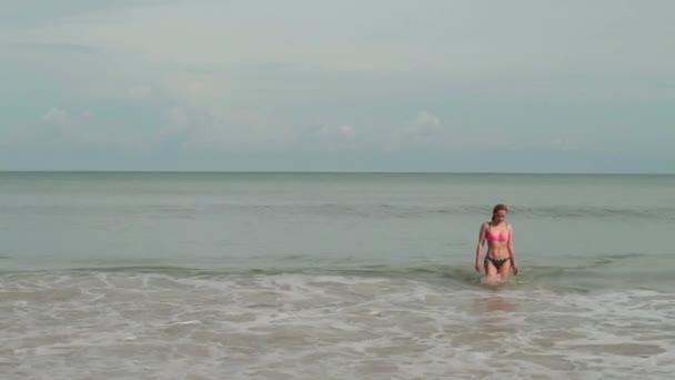 Fiatal nő a bikini, a tenger hullámok élvezi a napozás és a tengerparti nyaralás
