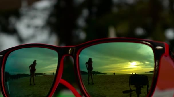 Sunglasses lying on the sand at sunset. In a sunglasses reflected sea, waves and sky.