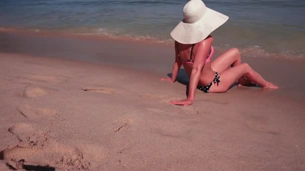 Nő a bikini és a fehér nap kalap-homokos tenger paradise strand napozás közben hátulnézet