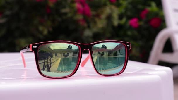 odraz ve slunečních brýlích dospívající dívky si v bazénu hotelu dovolenou. dvě sestry hrát, plavání a skoky do vody