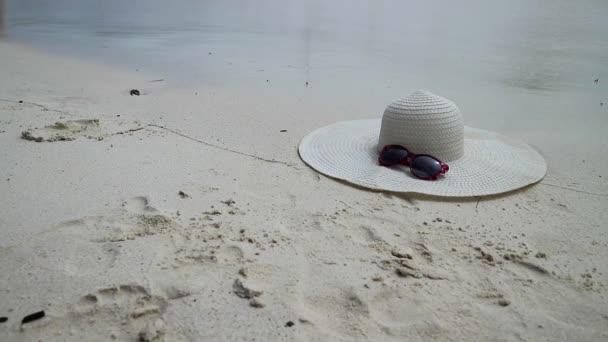 Sluneční brýle a bílá široká krempa ležící na písku. krajina s vlnami na písčitý břeh.