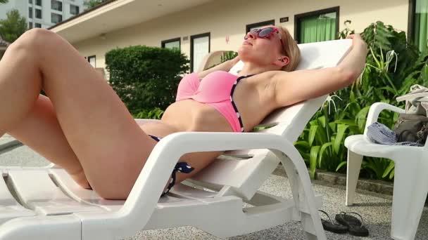 Gondtalan karcsú nő lecsavarható, és egy nyári napon a medence közelében sunbathes