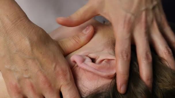 Kopf-Massage im Spa-Center. Kunde genießt die Dienste eines Masseurs. 4k